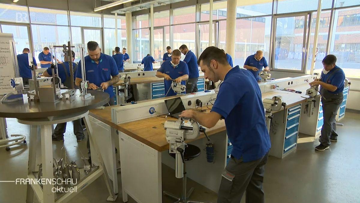 Mitarbeiter von Bosch arbeiten an Werkbänken.