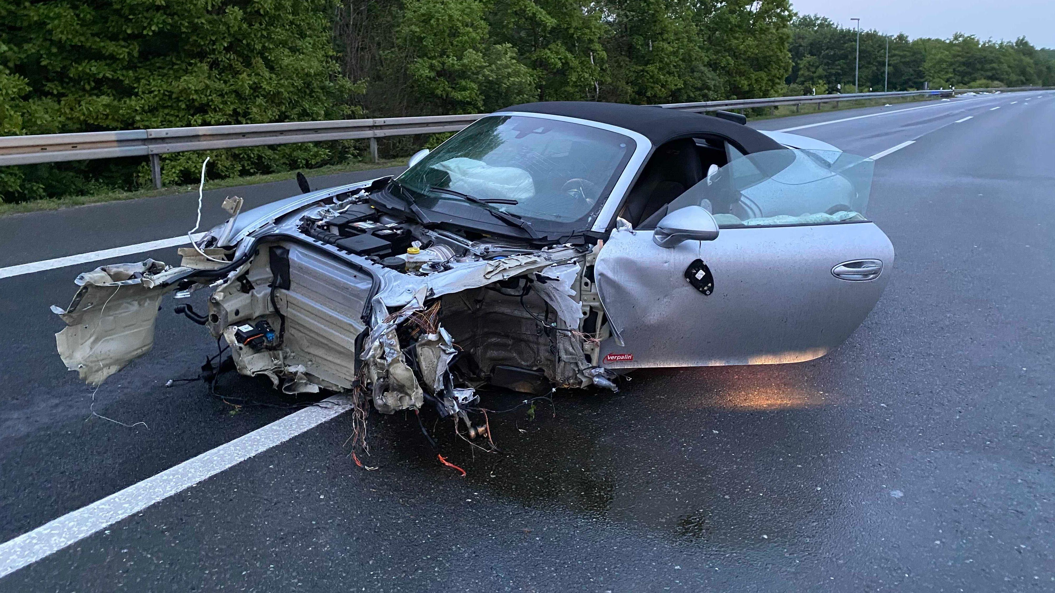 Ein nach einem Unfall völlig zerstörter Porsche steht auf der Fahrbahn.