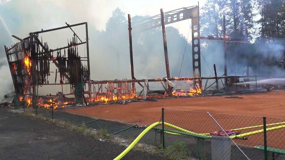 Einsatzkräfte der Feuerwehr löschen ein brennendes Holzgebäude.