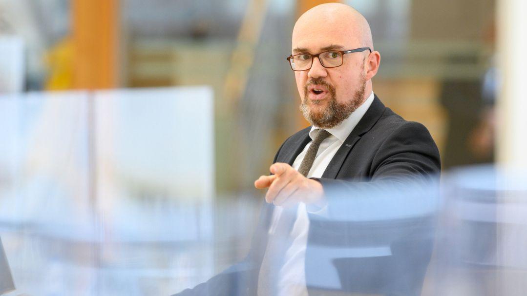 Hans-Thomas Tillschneider steht an einem Rednerpult und deutet mit dem Zeigefinger in Richtung Kamera.