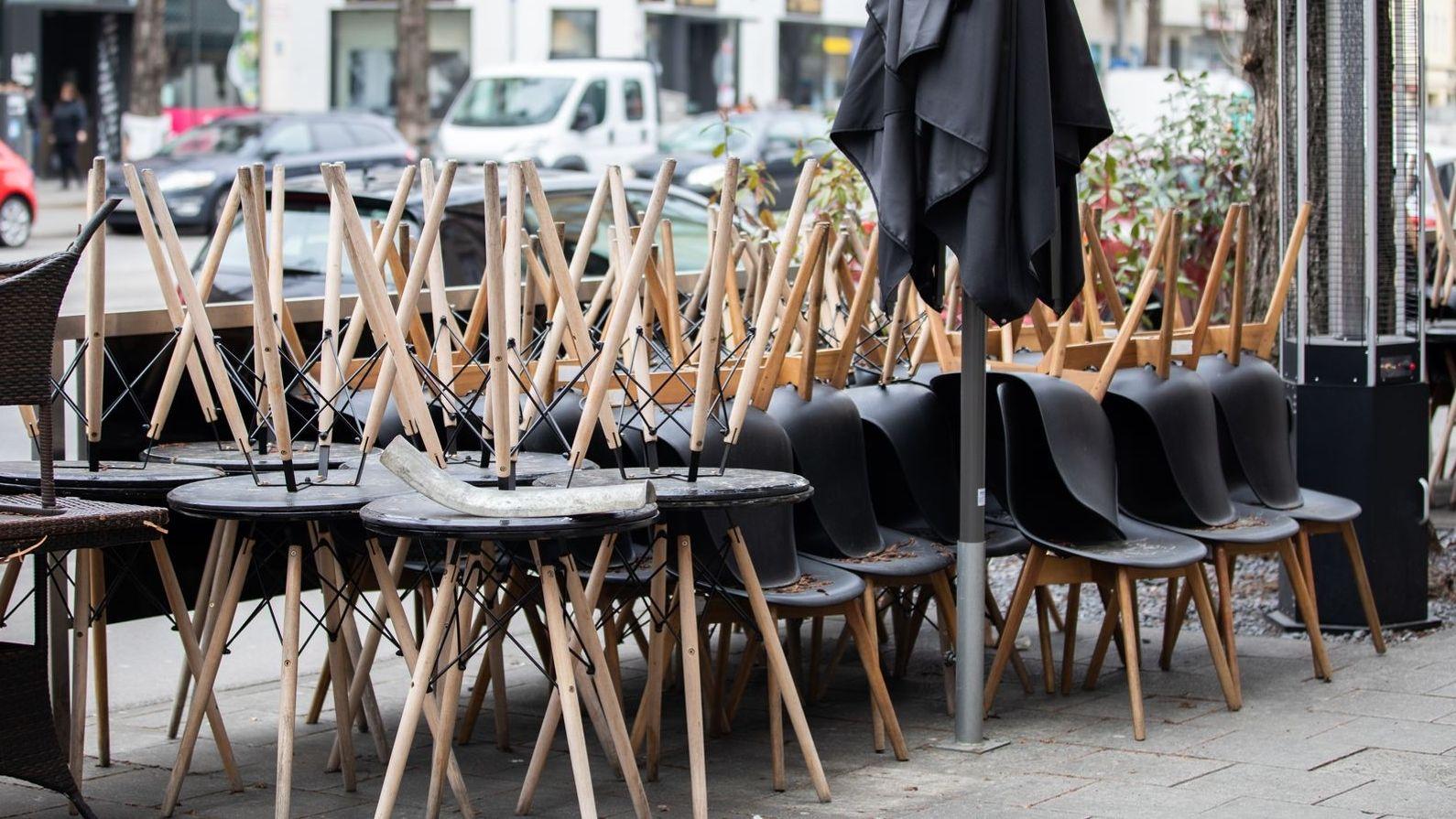 Stühle eines Lokals stehen draußen mit den Beinen nach oben aufeinander
