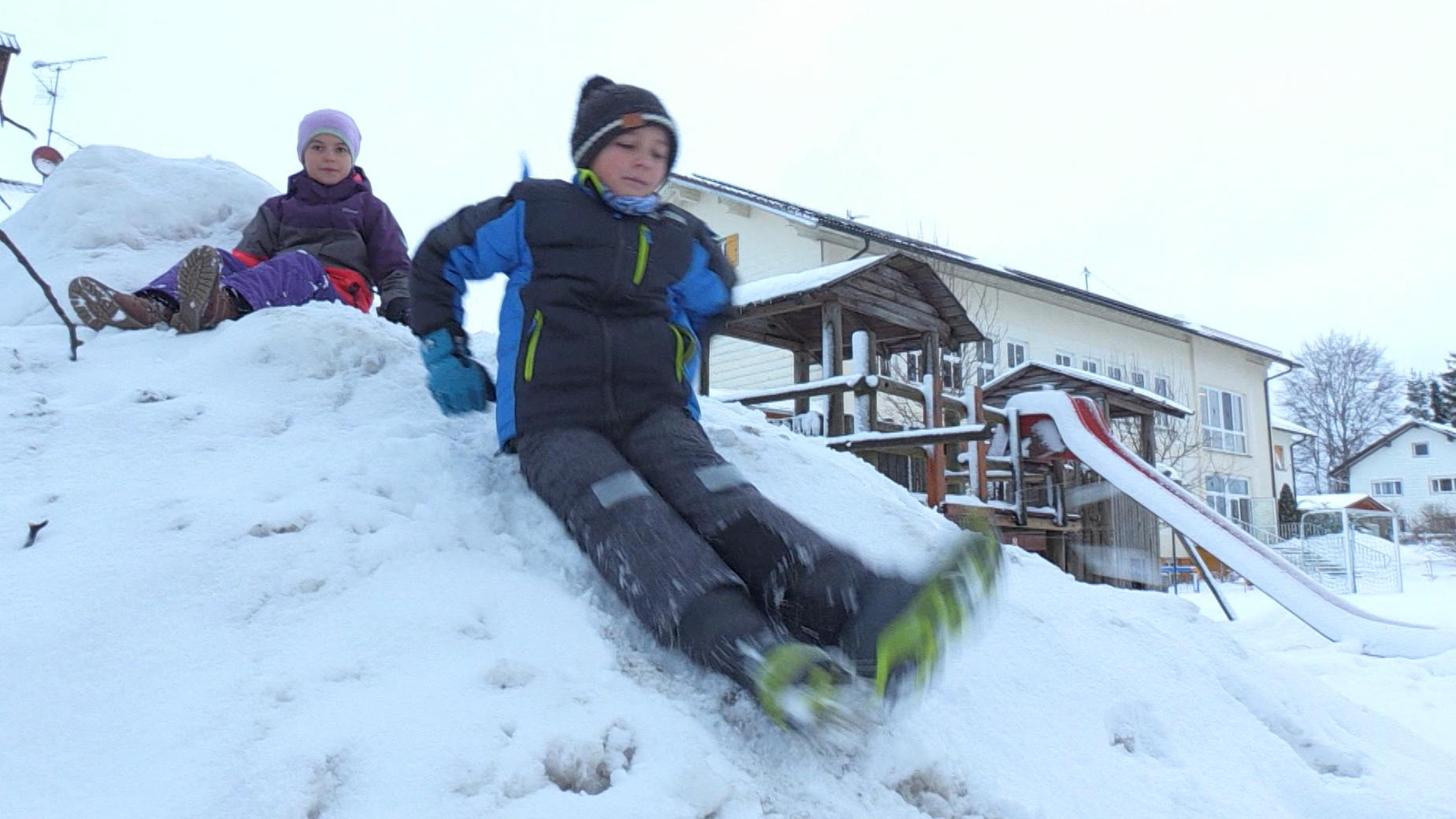 Kinder rutschen über einen Schneeberg