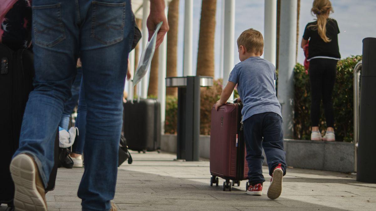 Ein Kind schiebt auf einem Flughafen in Spanien einen Koffer