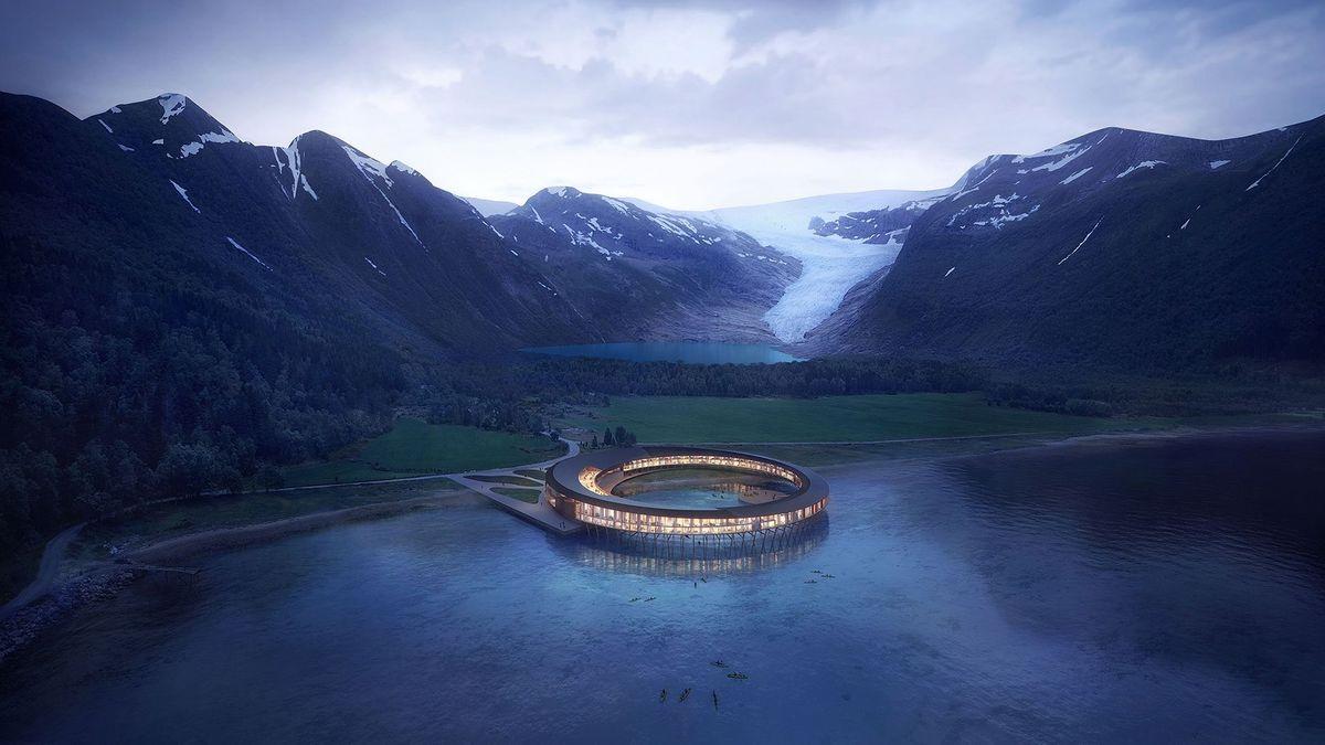 Ein in einen Bergsee gebautes, ringförmiges Hotel, dessen Fenster beleuchtet sind: Hotel Svart
