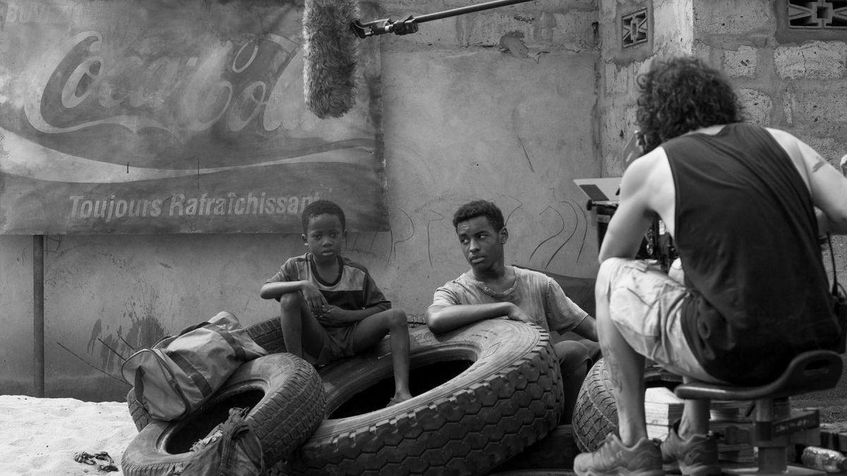 """Ein kleiner Junge aus Kamerun sitzt auf einem LKW-Reifen, über ihm baumelt ein Mikrofon. Die Szene wurde während der Dreharbeiten zu dem spanischen Film """"Adú"""" aufgenommen."""