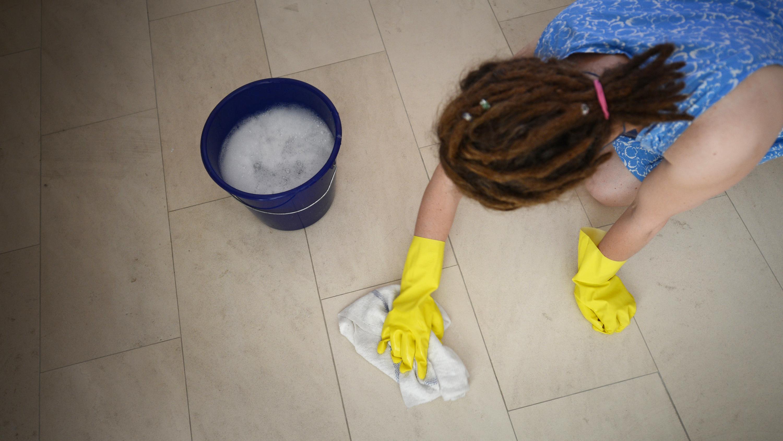 Eine Haushaltshilfe putzt den Boden.