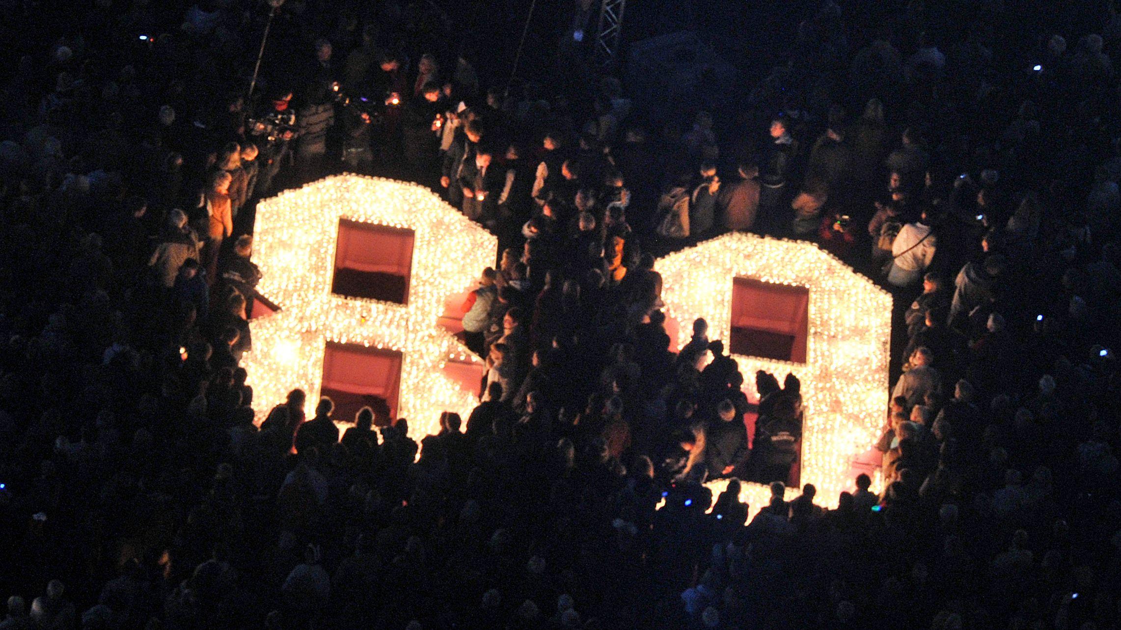 Menschen aus Leipzig erinnern an die Friedliche Revolution von 1989 und stellen die historische Zahl mit Kerzen dar.