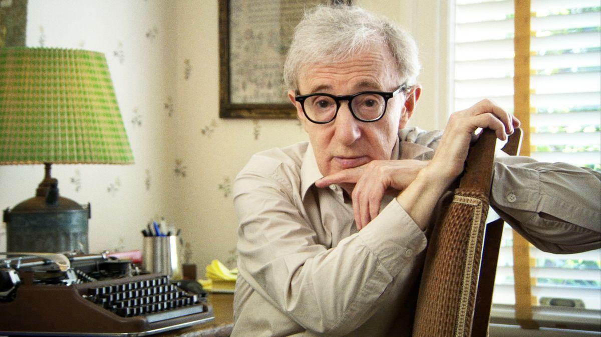 Bild von Woody Allen. Er sitzt an einem Schreibtisch mit einer Schreibmaschine und einer alten Lampe.