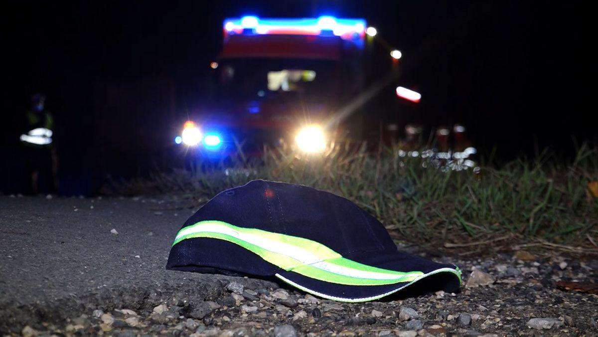 Eine Schirmmütze liegt am Straßenrand, im Hintergrund steht ein Krankenwagen