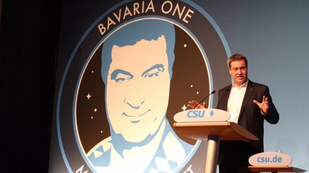"""Ministerpräsident Markus Söder vor dem """"Bavaria One""""-Logo der JU"""