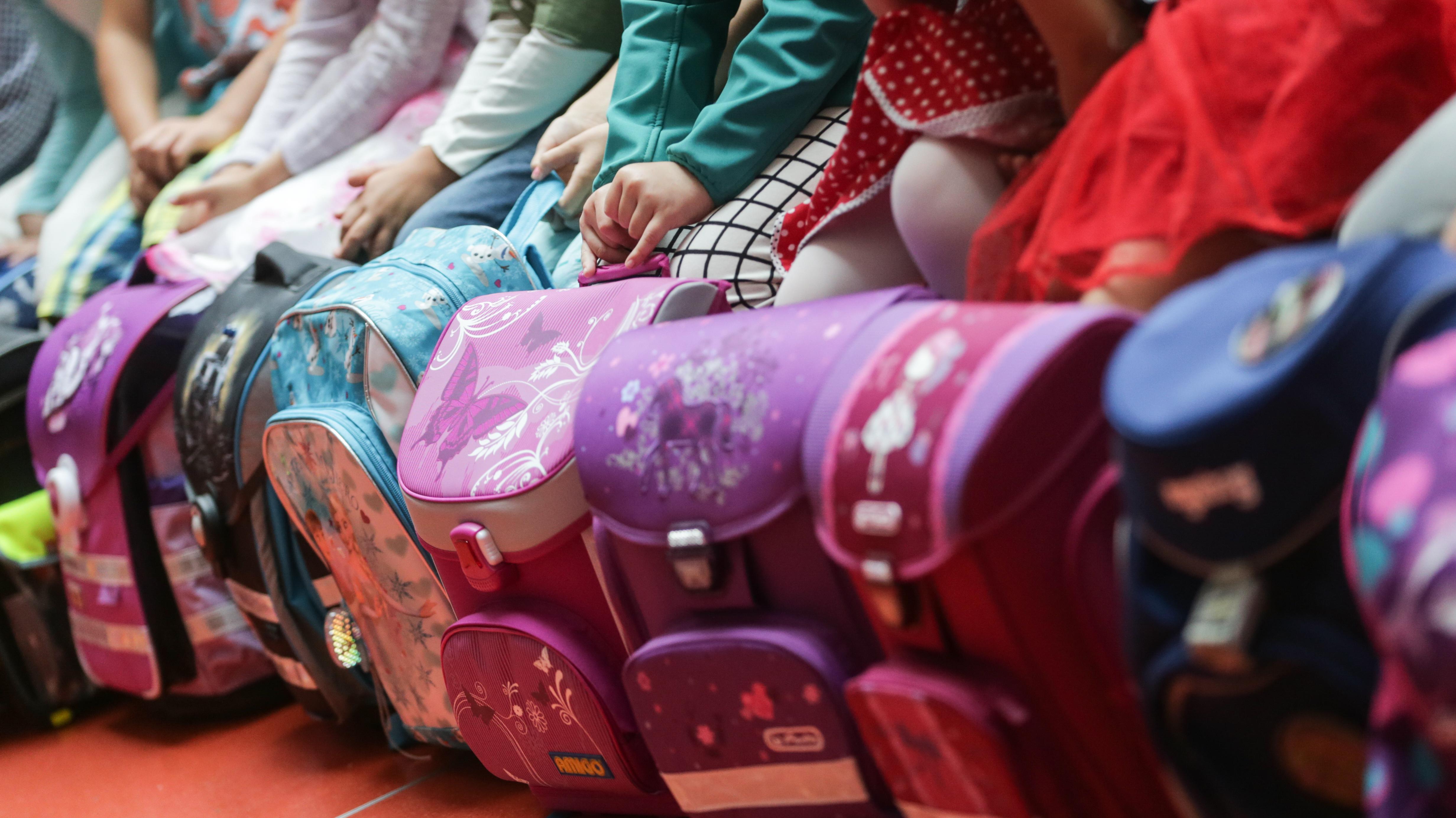 Erstklässler sitzen bei der Einschulungsfeier hinter ihren Schulranzen.