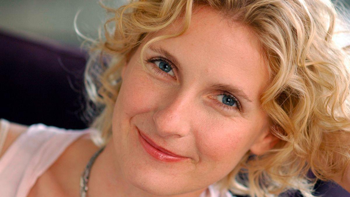 Das undatierte Foto zeigt die US-amerikanische Autorin Elizabeth Gilbert, mit blonden Locken, den Kopf in die Hände gestützt, lächelnd.