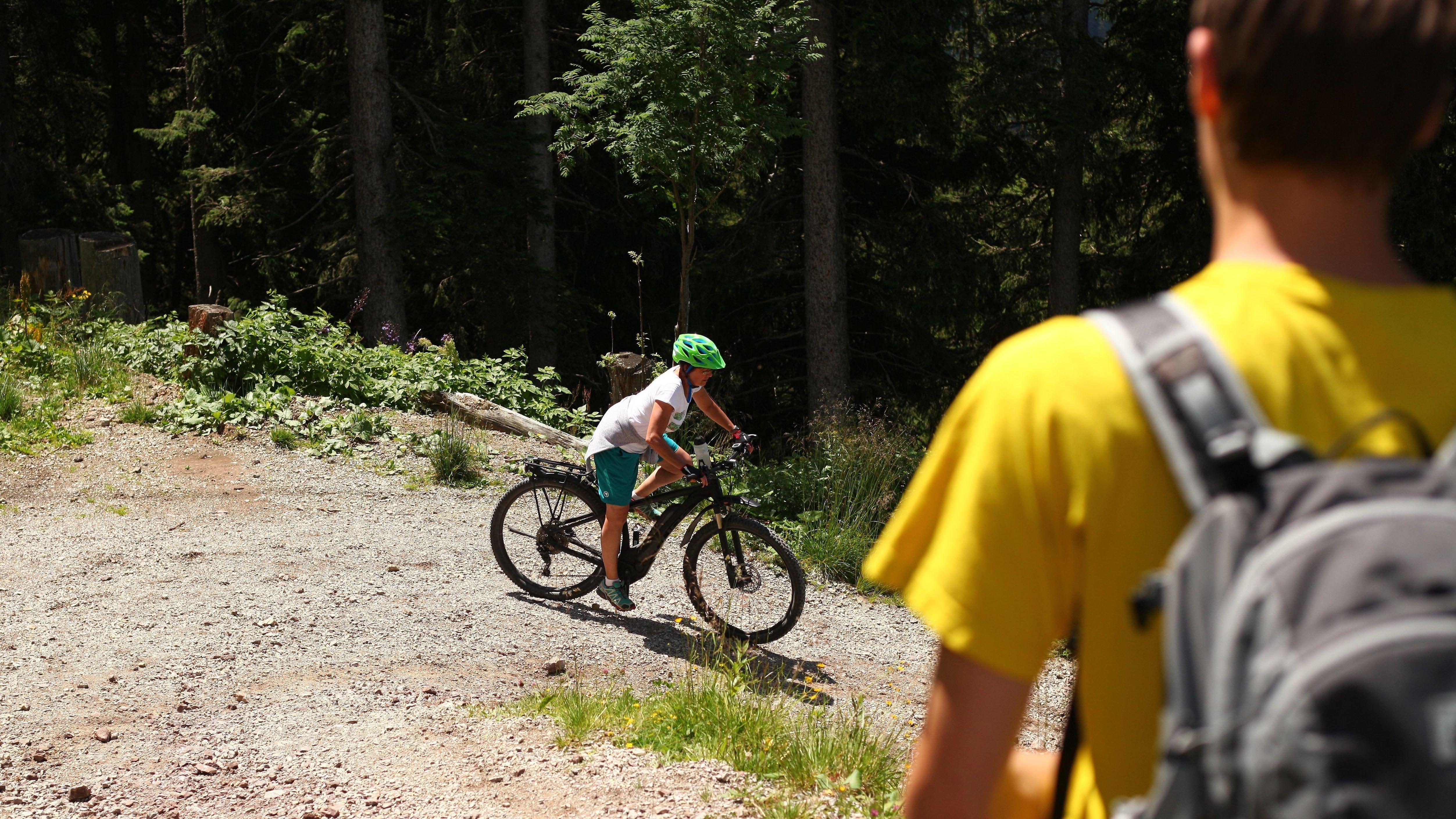 Eine Frau fährt auf einem E-Mountainbike vor einem Wanderer einen Berg herunter