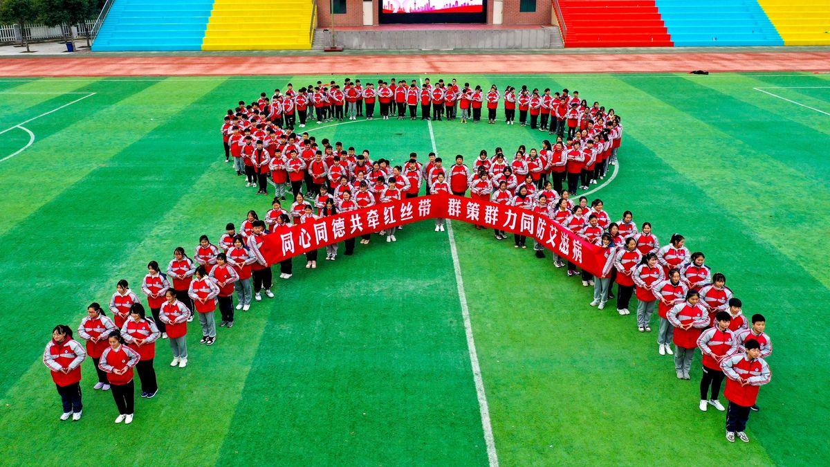 Athletinnen im roten Trikot bilden eine Schleifenform im Stadion