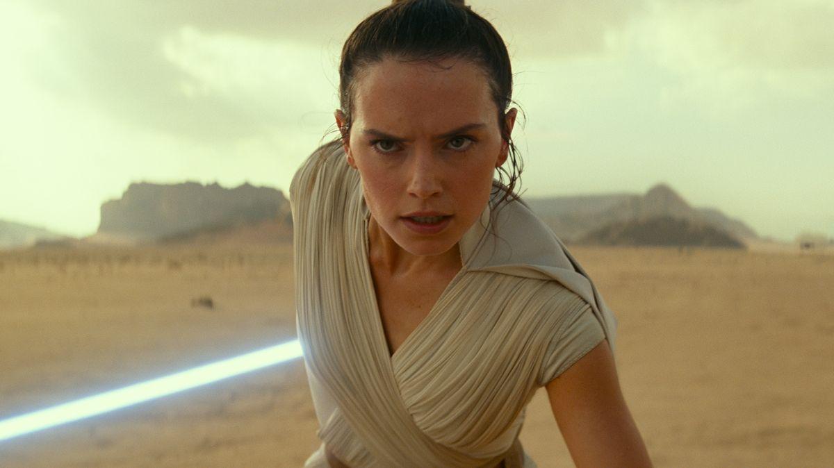 """Filmszene aus """"Star Wars 9"""": Kriegerin in antikischem Gewand stürmt in einer wüstenhaften Landschaft auf die Kamera zu, ein leuchtendes Laserschwert in der Hand"""