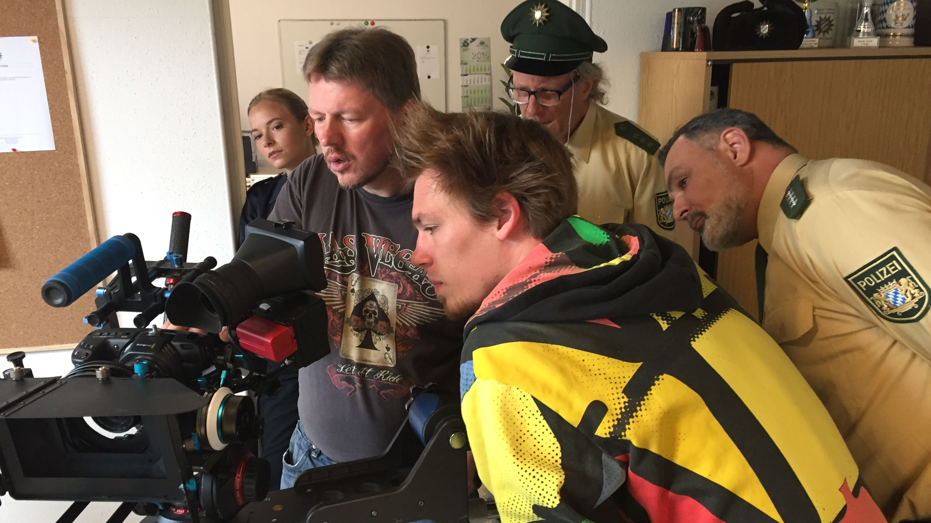 Regisseur, Schauspieler und Polizeibeamte schauen in einer Polizeistation durch das Objektiv einer Filmkamera