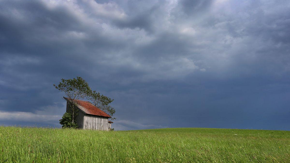 Dunkle Regenwolken ziehen über eine Holzhütte und eine Wiese
