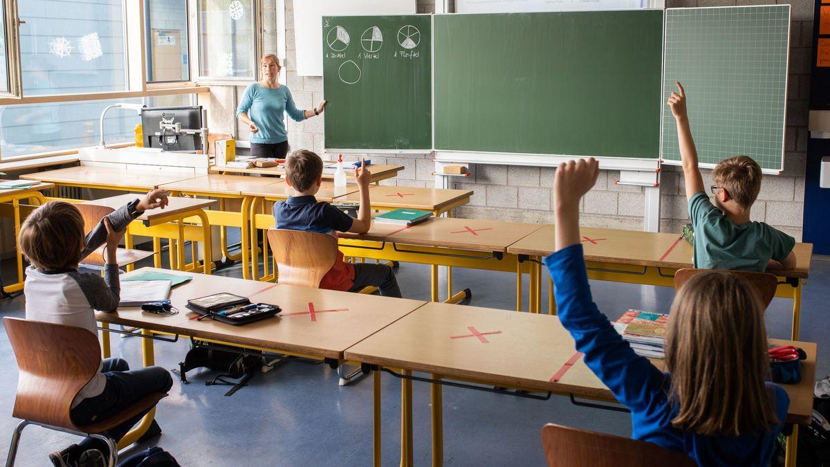 Schüler sitzen mit Abstand in einem Klassenzimmer, wo eine Lehrerin an der Tafel etwas erklärt.