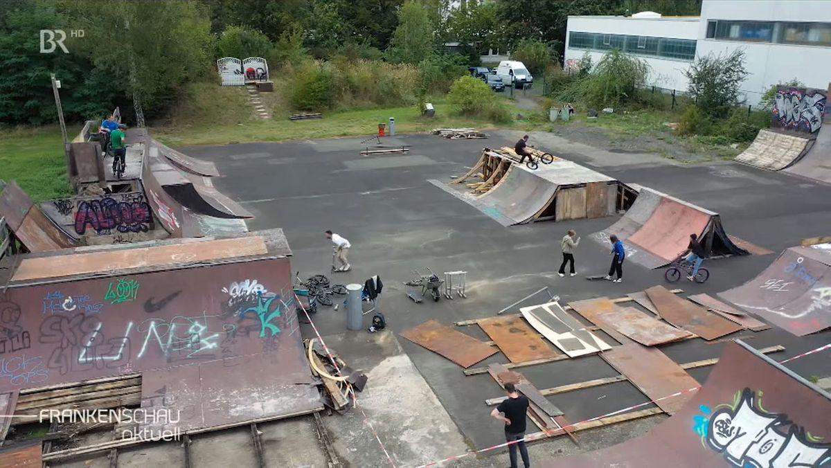 Der Skatepark in Coburg mit unterschiedlich großen und hohen Rampen, aufgebaut auf einer Asphaltfläche, von oben aus gesehen.