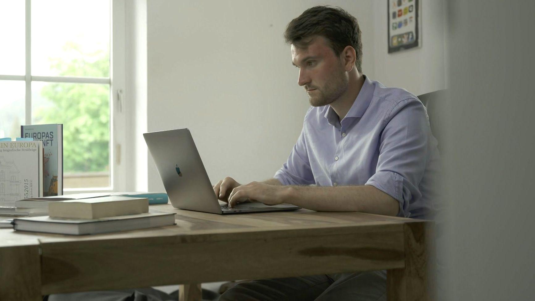 Junger Mann sitzt vor Laptop