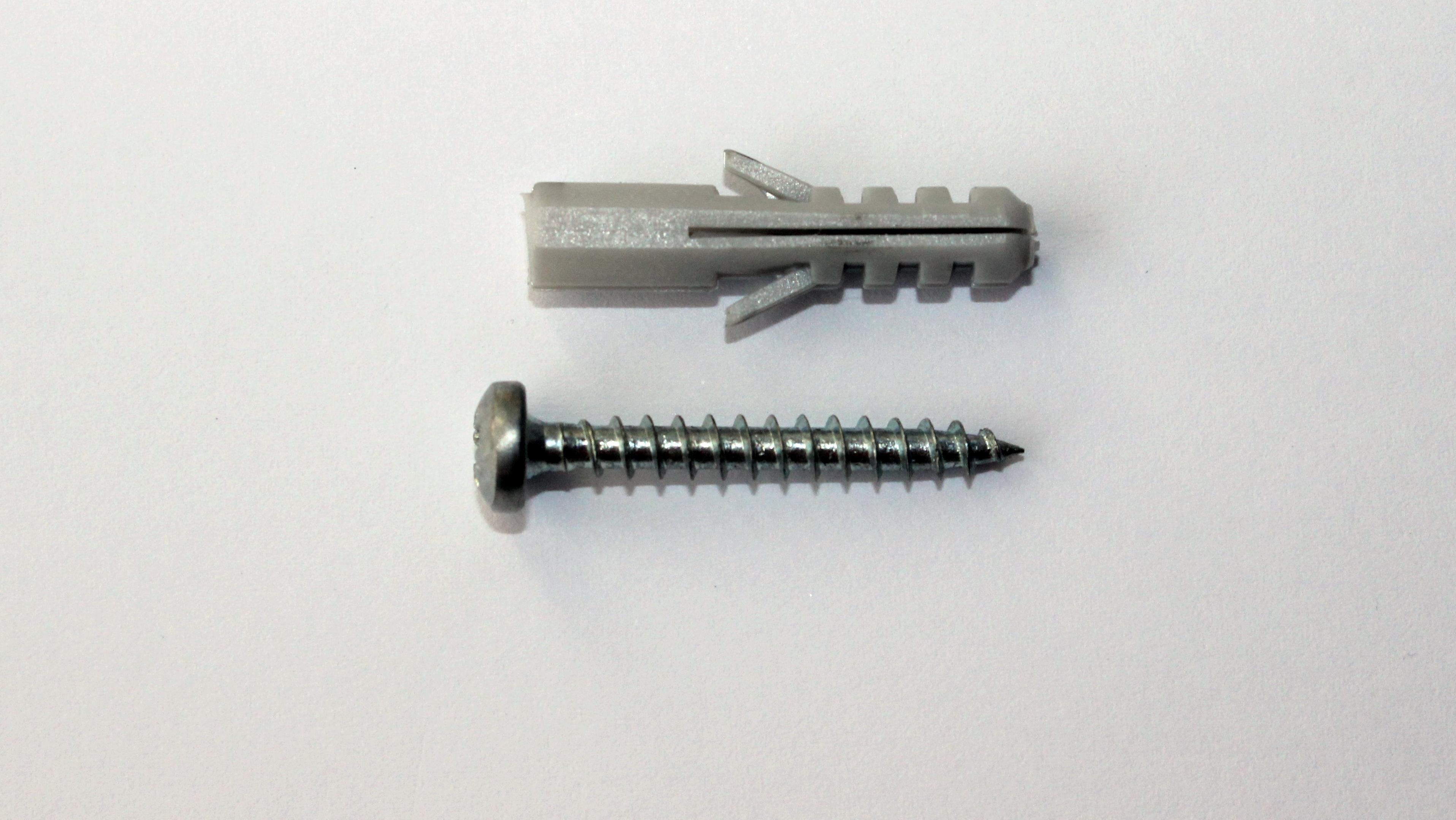 Ein Fischer-Dübel und eine passende Schraube liegen nebeneinander. Artur Fischer hat den Dübel erfunden und am 7. November 1958 zum Patent angemeldet.