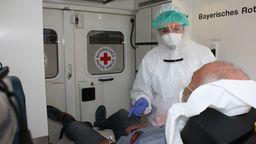 Mann und Sanitäterin in Schutzkleidung in einem Rettungswagen | Bild:BRK Traunstein