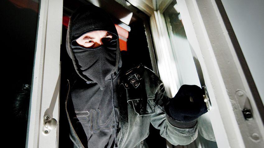 Ein Einbrecher öffnet ein Fenster - Symbolbild