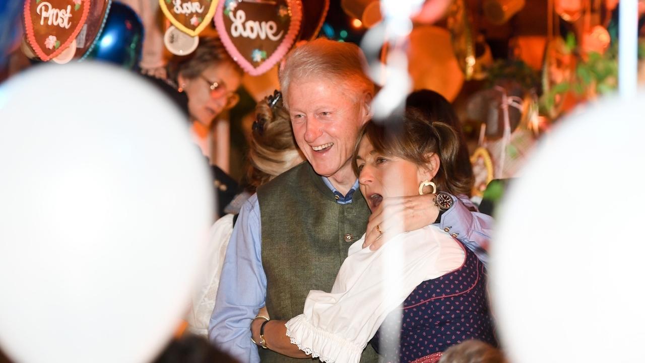 Bill Clinton, früherer Präsident der USA und ein Gast (unbekannt) umarmen sich im Käfer-Festzelt auf dem Oktoberfest.