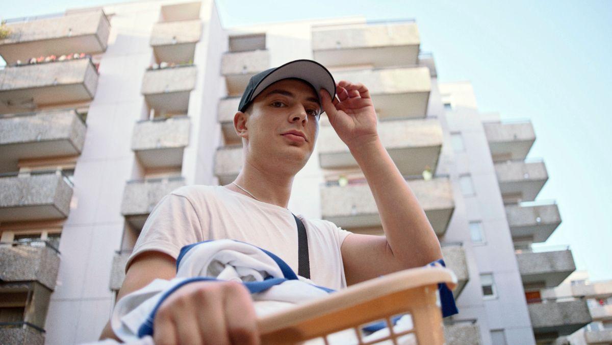 Ein junger Mann mit Baseballmütze und freundlichem Gesicht vor einem Hochhaus.