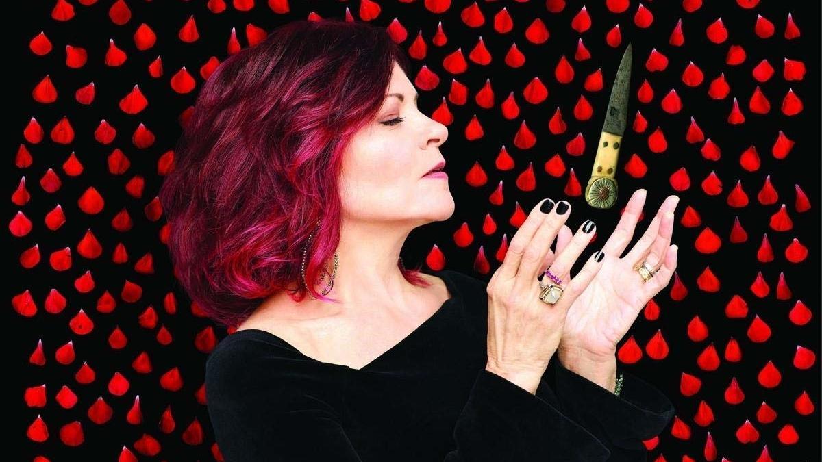 Rosanne Cash mit leuchtend roten haaren, in schwarzem Oberteil, im Hintergrund rote Blütenblätter, in ihren Händen ein uraltes Messer.