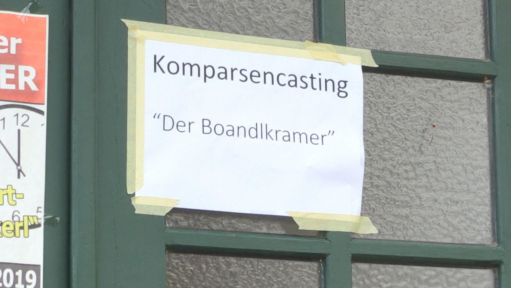 """An der Wirtshaustür hängt ein Schild mit der Aufschrift """"Komparsencasting ´Der Boandlkramer`"""""""