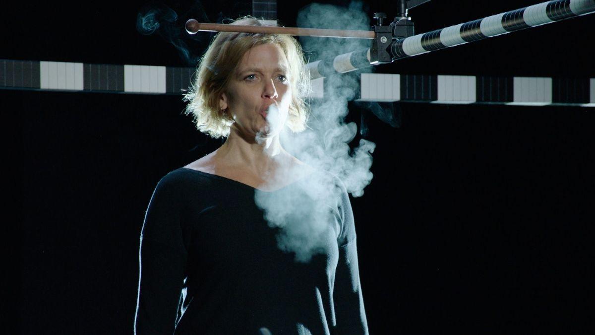 Eine Frau steht vor schwarzem Hintergrund und atmet aus. Ihr Atmen ist im Gegenlicht als Dampfwolke zu erkennen.