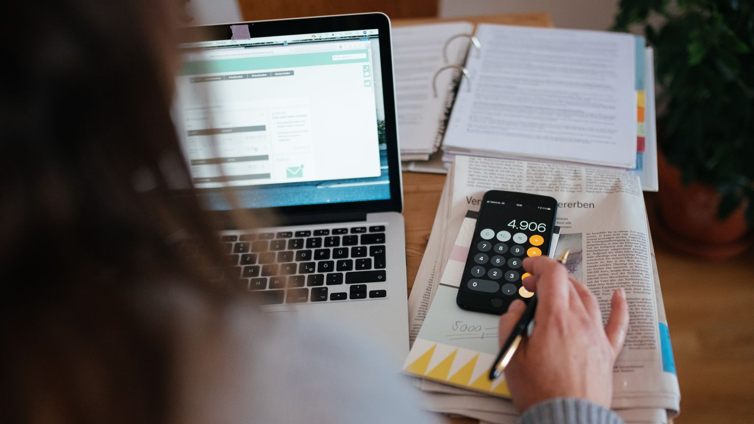Eine Frau sitzt vor Unterlagen und berechnet etwas mit ihrem Smartphone.