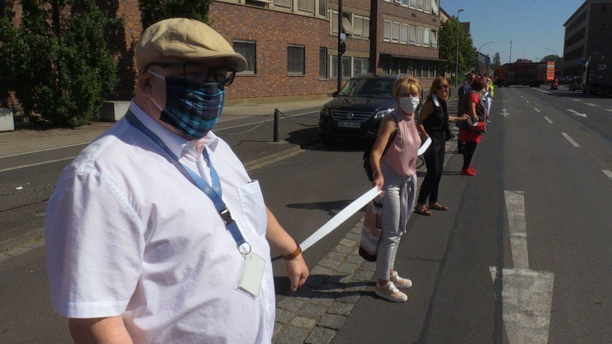 Mitarbeiter von ZF stehen aufgereiht entlang einer Strasse