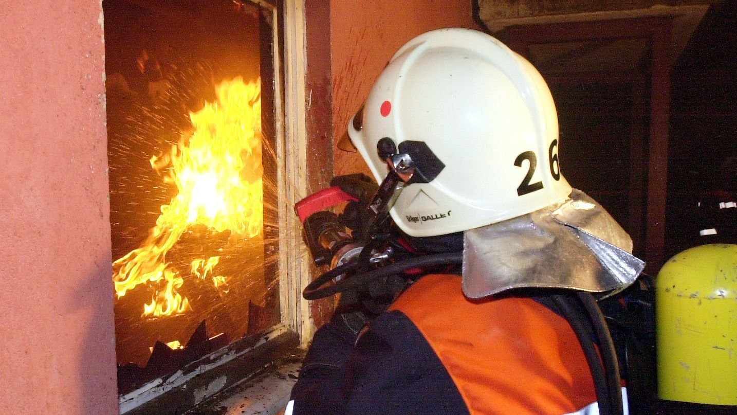 Ein Feuerwehrmann unter schwerem Atemschutzgerät versucht durch ein Fenster eines Wohnblocks ein Feuer zu löschen (Symbolbild)