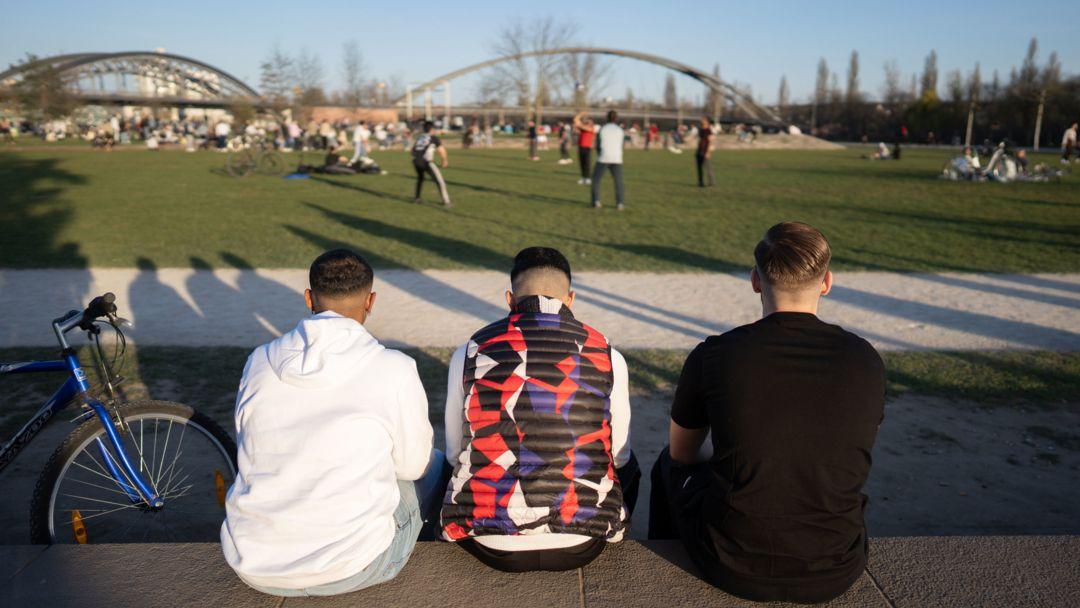 Frankfurt/Main: Drei junge Männer sitzen bei sonnigem Wetter auf einer Mauer im Hafenpark.