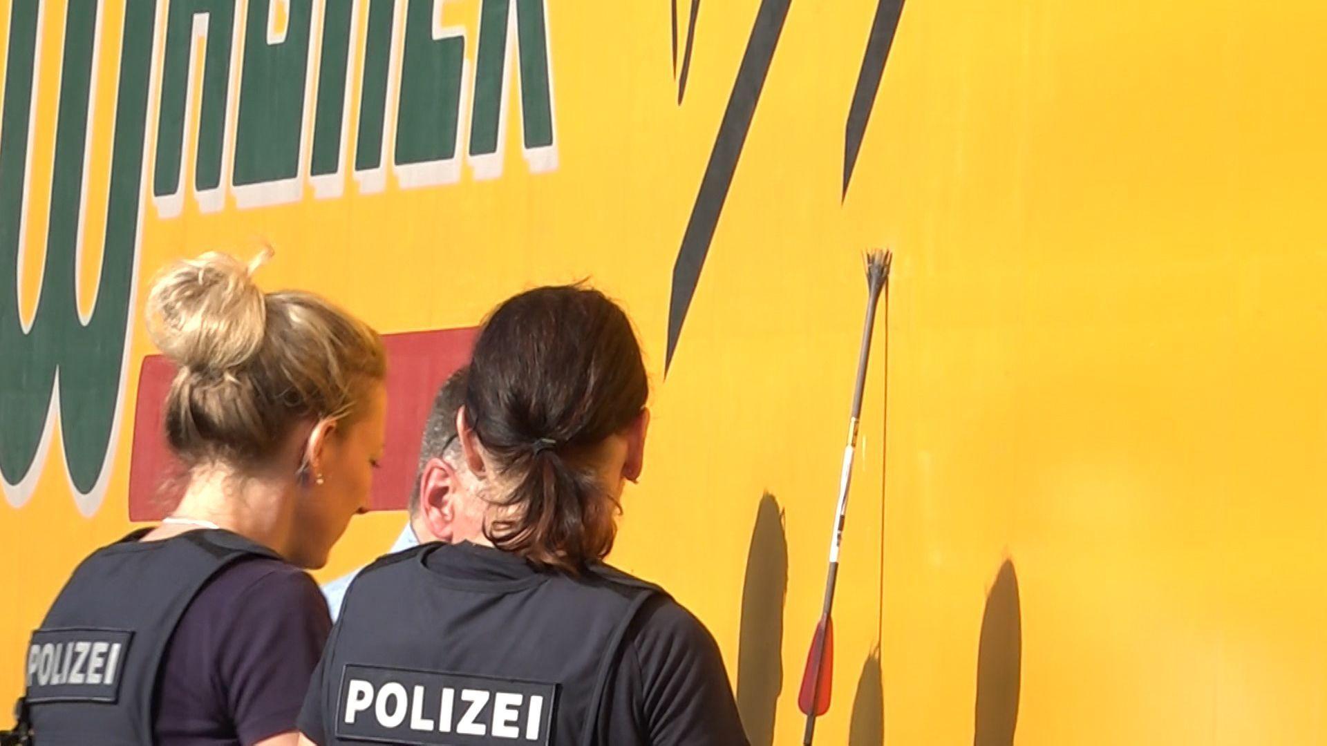 Polizistinnen mit einem der Pfeile, der in einem Lkw stecken geblieben ist.
