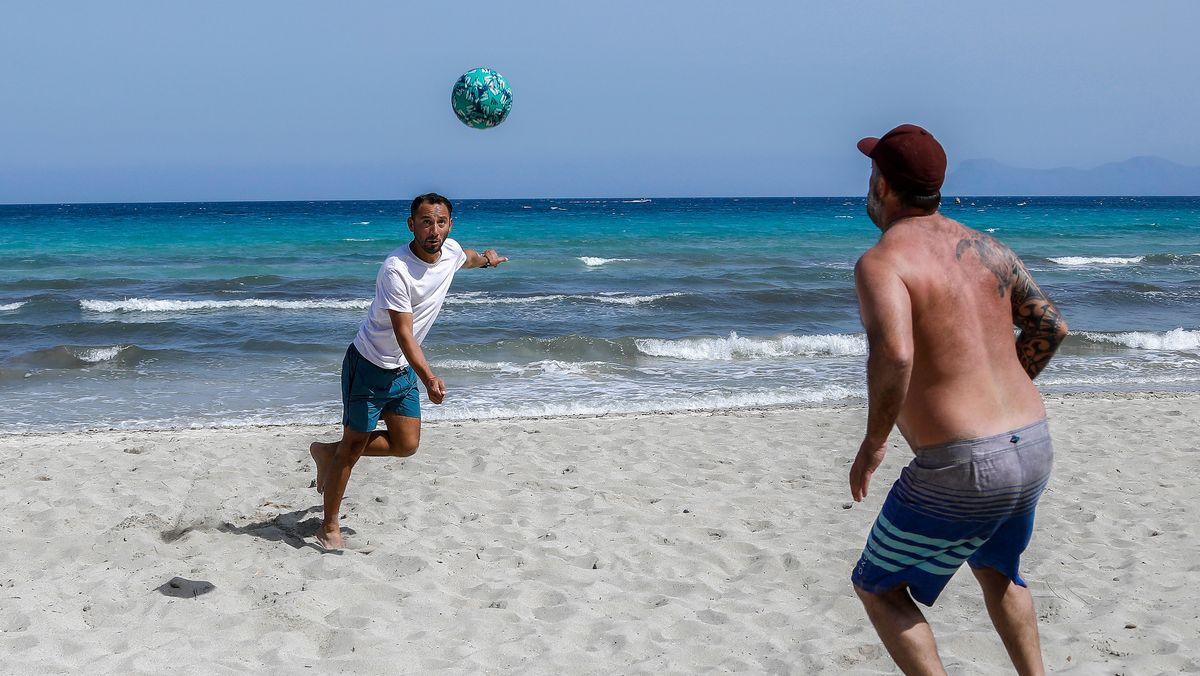 Zwei Spanier spielen Volleyball am Strand.