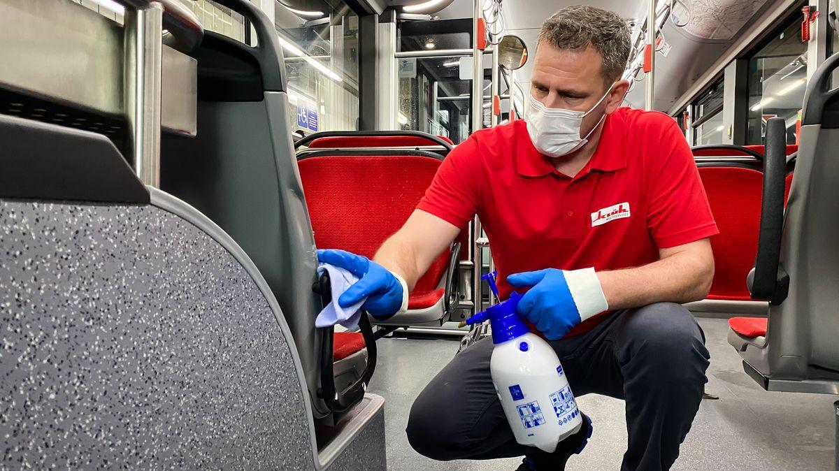 Mann putzt einen Bus.