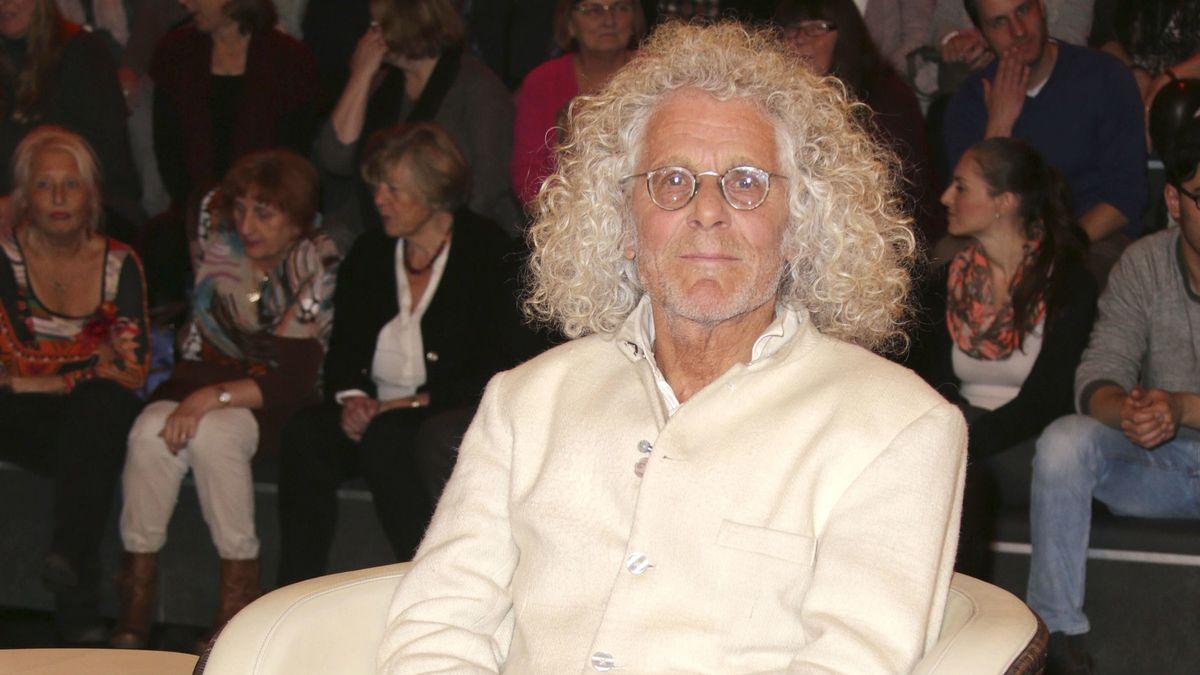 Ein graugelockter alter Mann mit runder Brille in weißer Jacke im weißen Talkshow-Sessel vor Publikum