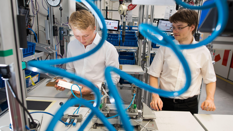 Zwei junge Männer stehen vor einer Apparatur