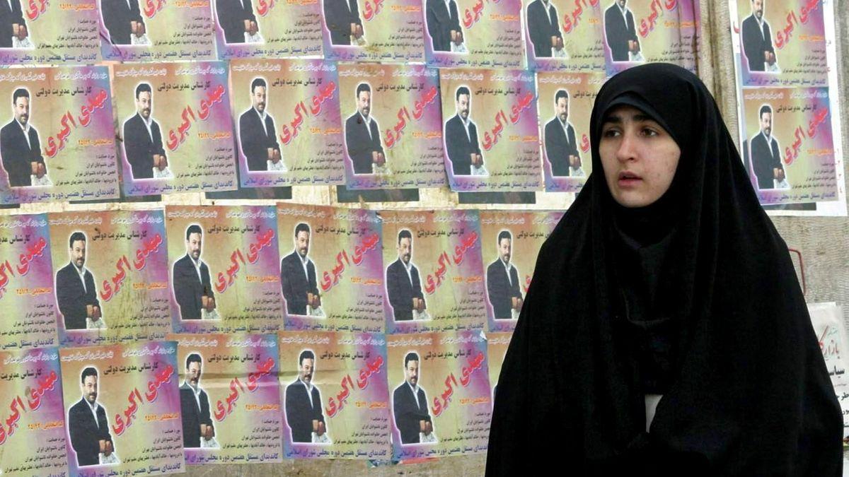 Iranische Frau vor einer Wand mit Wahlplakaten