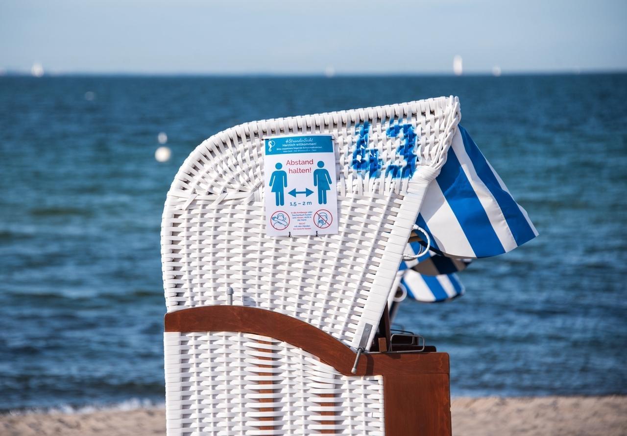 ARCHIV - 21.05.2020, Schleswig-Holstein, Niendorf/Ostsee: «Abstand halten» steht auf einem Schild an einem Strandkorb am Strand an der Ostsee. Mit Blick auf fortschreitende Lockerungen und die bevorstehende Urlaubszeit erinnern Experten an das Risiko eines erneuten Anstiegs von Corona-Neuinfektionen. Foto: Daniel Bockwoldt/dpa +++ dpa-Bildfunk +++