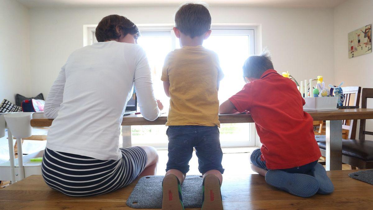 Eine Mutter sitzt Zuhause neben ihren Kindern, während diese malen und ein Buch ansehen.