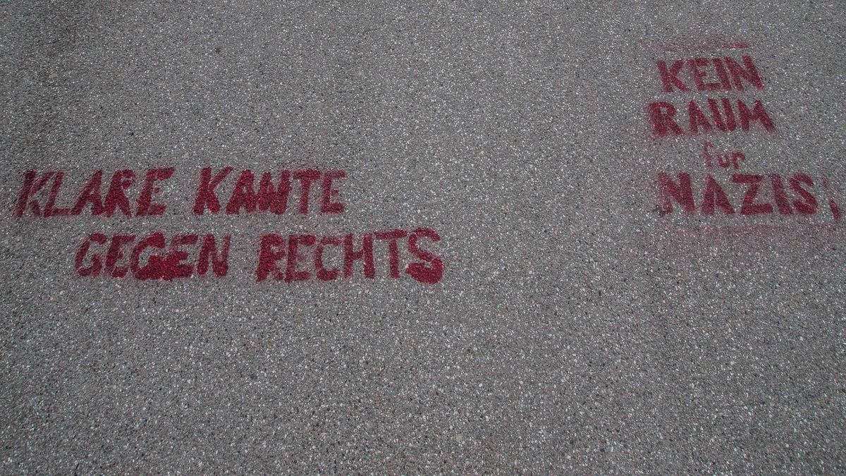 """Schriftzüge ''Klare Kante gegen Rechts'' und """"Kein Raum für Nazis"""" sind auf eine Straße gesprüht."""