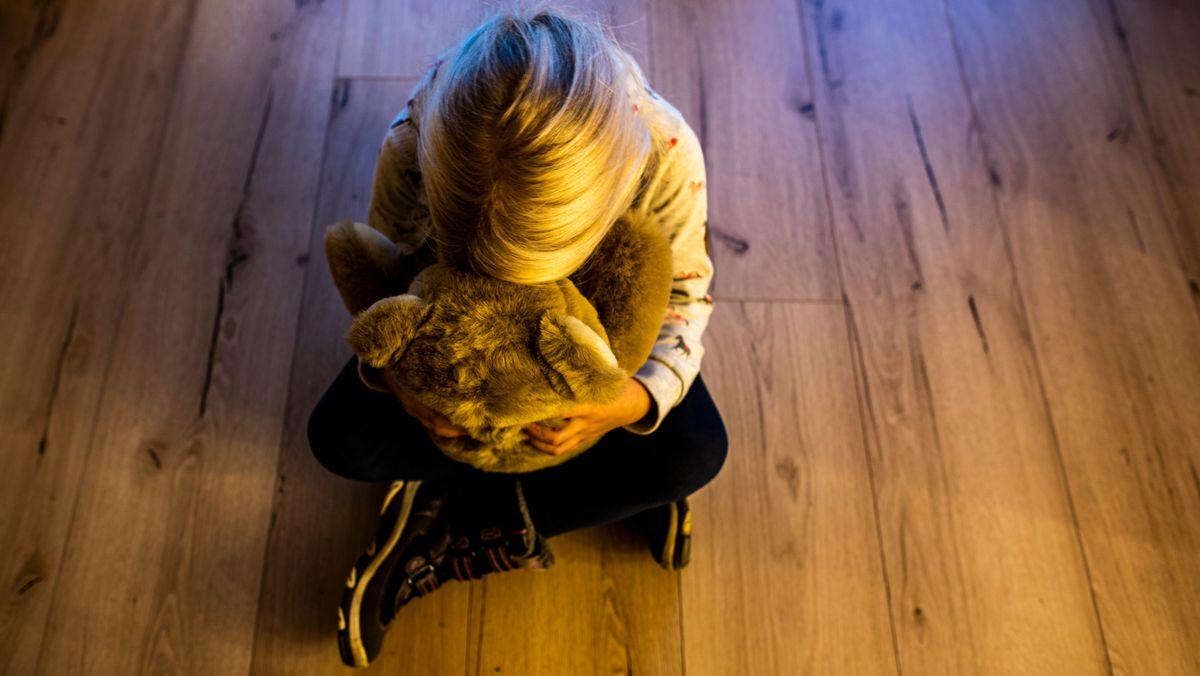 Ein Mädchen versteckt ihr Gesicht in einem Teddybär und sucht Trost. (Symbolbild)