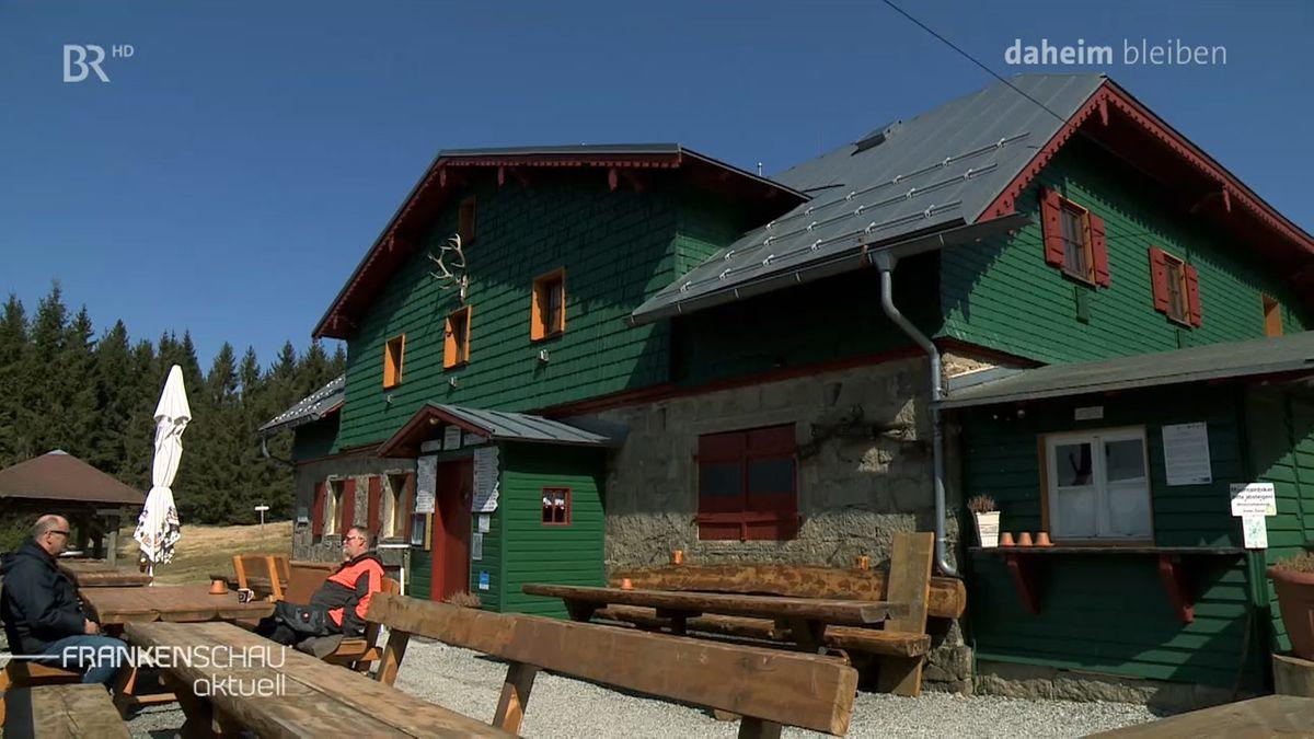 Vor einer Hütte im Fichtelgebirge sitzen zwei Wanderer auf einer Holzbank, die anderen Plätze sind nicht besetzt.