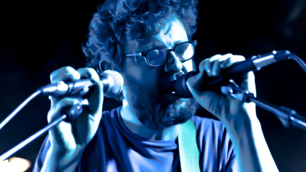 Sänger in blauem Bühnenlicht singt mit Brille und geschlossenen Augen konzentriert ins Mikrofon.