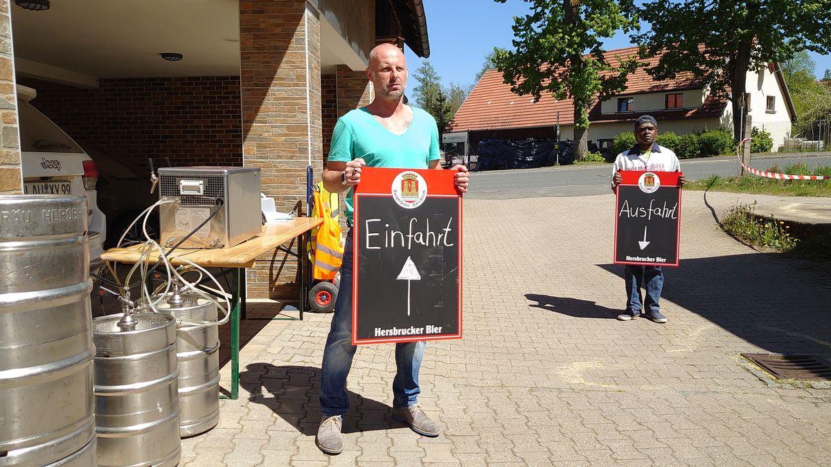 """Personen halten Schilder mit """"Einfahrt"""" und """"Ausfahrt"""" hoch"""