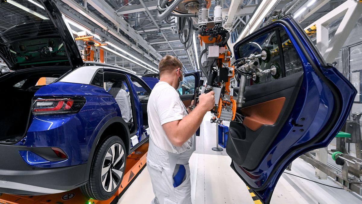 Ein Mitarbeiter im Volkswagenwerk in Zwickau komplettiert einen Elektro-SUV.